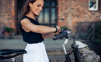45175302 - young woman with a bike checking the time on her wristwatch. happy woman with bicycle looking at watch, outdoors.