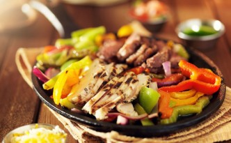 44656754 - mexican steak and chicken fajitas in iron skillet with bell peppers and onion shot with warm colored light
