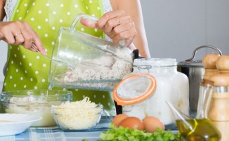 49216487 - happy young woman preparing chicken pate in domestic kitchen